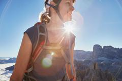 Female hiker hiking in sunlit Dolomites, Sexten, South Tyrol, Italy Stock Photos