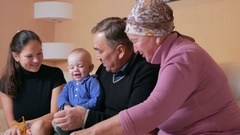 Big happy family with a baby her mother and grandparents have fun at home on the Stock Footage