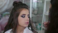 Make up artist attach false eyelashes slow motion Stock Footage