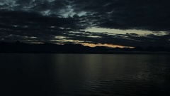 Darkening Clouds and Sunset Mountains Silhouette Waters Stock Footage