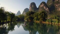 People taking bamboo raft along Yulong River, Yangshuo, Guangxi, China Stock Footage