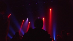 Crowd at rave party, people dance in blue light of projectors Stock Footage