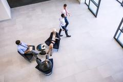 High angle view of businesswoman and men meeting in office atrium Stock Photos