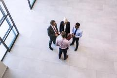 High angle view of businesswoman and men having discussion in office atrium Stock Photos
