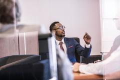 Window view of businessman questioning in board meeting Stock Photos