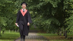 Smiling young man in academic dress walking and jumping, way to future success Stock Footage