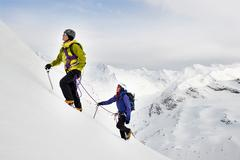 Mountaineers ascending snow-covered mountain, Saas Fee, Switzerland Stock Photos