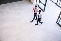 High angle view of two businessmen arriving in office atrium Stock Photos