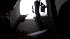 Woman passenger writing with pen and paper airplane in flight by bright window Stock Footage