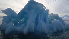 Boat track past intricate iceberg, Antarctica Stock Footage