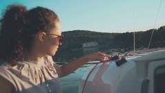 Attractive young girl looks afar floating the sailboat Stock Footage