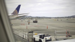 Aircraft parked on runway with orange cones and workers at San Francisco Airport Stock Footage