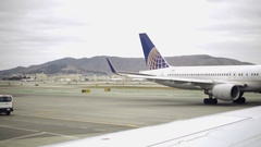 United Airlines plane tail driving on runway with mountains background Airport Stock Footage