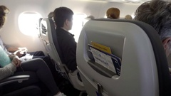 Airplane cabin interior with passengers sitting in seats on bright sunny day Stock Footage