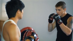 Two guys are training mixed martial arts in the hall fighting arts Stock Footage