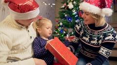 Little girl unboxing christmas gift. Medium shot Stock Footage