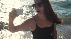 Attractive girl makes selfie on the seacoast Stock Footage