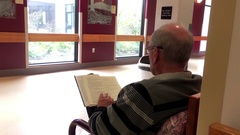 Motion of patient walking through hospital corridor while people reading novel Stock Footage
