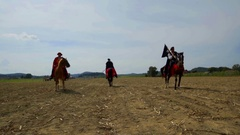 Three knights on horses are standing in the middle of a big field Stock Footage