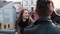 Young beautiful girl talks to two men, emotionally laughs. Red-haired man Stock Footage