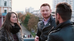 Young pretty girl and a red-haired man talk to another man standing near a Stock Footage