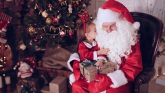 Little girl sitting in the hands of Santa Claus near Christmas tree Stock Footage