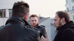 Three men with beards talk. A young red-haired man in the centre, two other Stock Footage