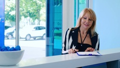 Woman fill the form at the reception in the cosmetology clinic Stock Footage