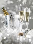 Two champagne glasses, a cooler with cork and silver decoration, stylish tinted Stock Photos