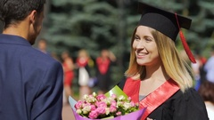 Beautiful female graduate receiving flowers and congratulations from male friend Stock Footage