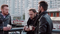 Three handsome young men with beards have a conversation and coffee on the go Stock Footage