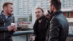 Three handsome young men with beards talk, smile and have coffee on the go near Stock Footage