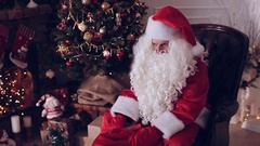Santa Claus sitting near Christmas tree with a bag full of presents Stock Footage