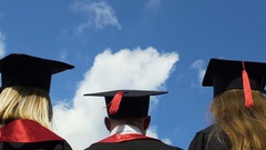Happy young people celebrating graduation, throwing academic hats up in air Stock Footage