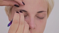 Close up shot. Professional make-up artist combing, plucking eyebrows of client Stock Footage