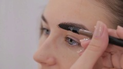 Professional make-up artist drawing eyebrows Stock Footage