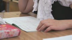 Schoogirl writes text in a notebook on a lesson Stock Footage