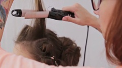 Close up shot. Professional hairdresser, stylist making curls on customer Stock Footage