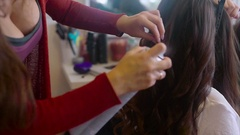 Close up shot of hairdresser sprays hairspray on brunette while making hair-do Stock Footage