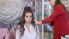 Hairstylist sprays hairspray on brunette model while making hair-do. Stock Footage