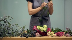 Florist prepares cut fresh flowers for a mixed bouquet arranging Stock Footage