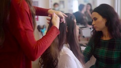 Hairstylist making hair-do with hair iron while make up artist applying cosmetic Stock Footage