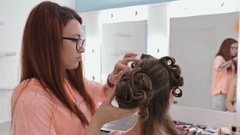 Hairdresser finishing hairstyle for young pretty woman Stock Footage