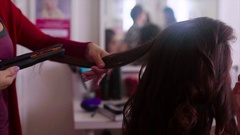 Close up shot of hairstylist making hair-do with hair iron slow motion Stock Footage