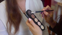 Close up shot of makeup artist taking eye shadows from make up palette Stock Footage