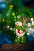 Snowman with a broom on a background of blurred Christmas tree Stock Photos