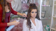 Hairstylist sprays hairspray on brunette while making hair-do Stock Footage