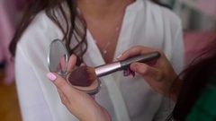 Close up shot of make-up artist taking powder by brush Stock Footage
