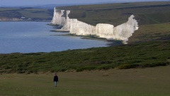 Rambling or walking solo - female atop South Downs white cliffs Stock Footage
