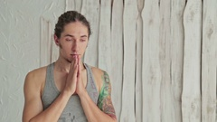 Young sporty man practicing yoga in fitness studio making hand greeting namaste Stock Footage